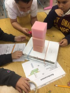 Students build foam structures on a shake table to learn about eathquake-resistant buildings.