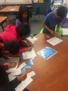 Students roll dice and read cards as part of the Water Cycle game.