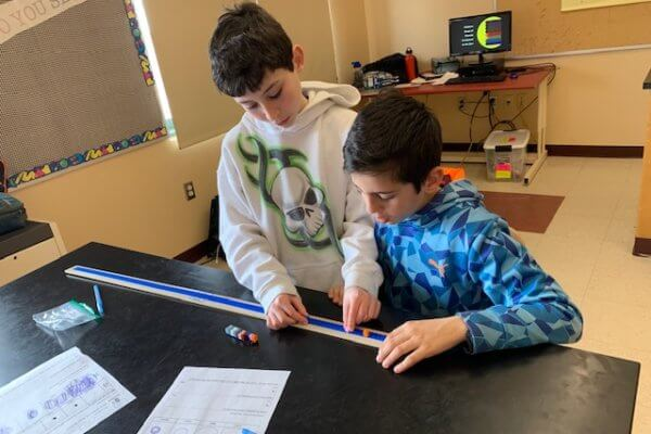 Students place Legos on a measuring stick to model how far apart the planets are in the solar system.