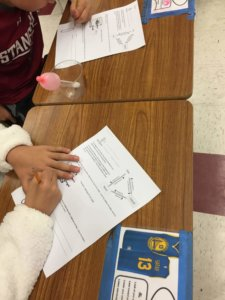 Students watch dry ice sublimate and fill a balloon with gas.