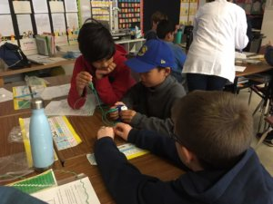 Students pick up paperclips with an electromagnet.