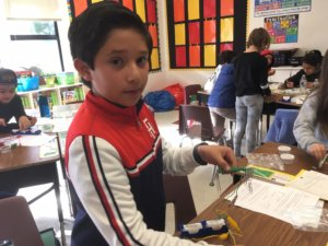 A student picks up paperclips with an electromagnet.