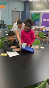 Students tip a tray to measure friction.