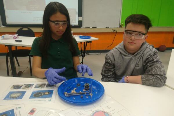 Students wearing goggles and gloves dissection an eyeball.