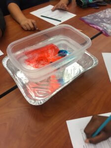 A container showing blue and red water mixing to demonstrate air masses.