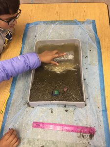 Students model beach erosion in a model beach.