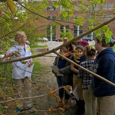 Students stand outside under a tree as a scientist speaks with them.