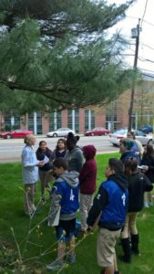 Students stand outside under a tree as a scientists speaks with them.