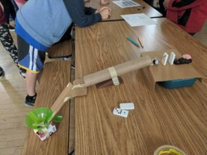 Students build Rube Goldberg devices.