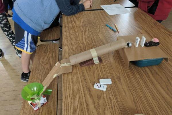 Students build Rube Goldberg devices.