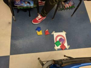 Students toss beanbags at a target taped to the floor.