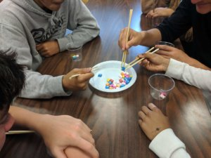 Students use chopsticks to fish as part of a sustainability investigation.