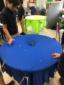 Students roll marbles on a gravity well.