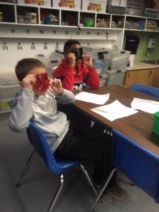 Students look through red and green color filters.