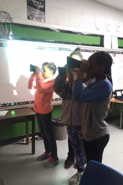 Students look at light through a spectrascope.