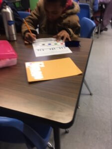 A student fills out a worksheet on light.