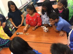 Students vertically stack dominos in a row leading up to a bell