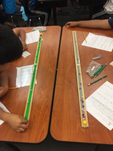 Students put Legos on a yard stick to model distances in the solar system