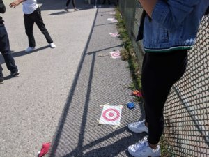 Students look at targets through prism goggles