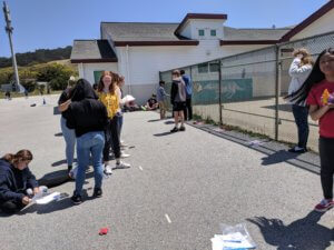 Students throw beanbags at a target while wearing prism goggles