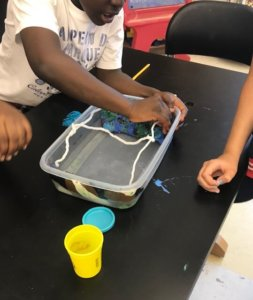 Students build a bridge with play dough and string