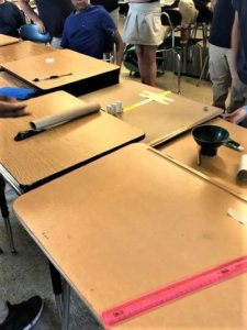 Paper towel tubes and rulers are laid out on desks