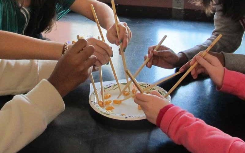 Students using chopsticks to fish.